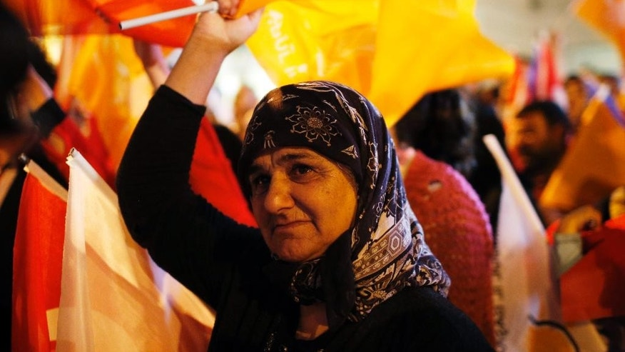 A supporter of Turkey's ruling Justice and Development Party celebratesafter the election results came out in Istanbul,Turkey, late Sunday, June 7, 2015. With 99.9 percent of the vote counted, President Recep Tayyip Erdogan's AKP had the support of around 41 percent of voters, state-run TRT television said. The unexpected setback for AKP likely puts an end, for the time being, to Erdogan's hopes of passing constitutional changes that would have greatly boosted the powers of his office. Instead, he faces struggles to retain his pre-eminent place in Turkish politics without the obvious levers to steer the government through his party in parliament. (AP Photo/Emrah Gurel)