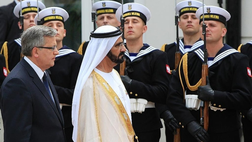 Polish President  Bronislaw Komorowski ,left, and Prime Minister of the United Arab Emirates Sheik Mohammed bin Rashid Al Maktoum inspect the honor guards during a ceremony at the Presidential Palace in Warsaw, Poland, Monday, June 8, 2015. (AP Photo/Czarek Sokolowski)