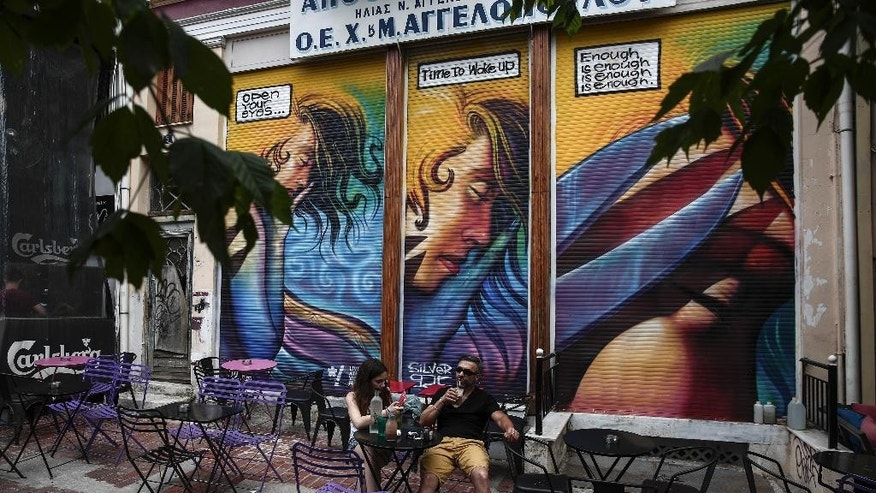 "People sit at a cafe in front of a graffiti covering the fence of a closed old textile shop in Athens, Greece, on Sunday, June 7, 2015.  Greece cannot accept the ""irrational"" proposal made this week by its bailout creditors, Prime Minister Alexis Tsipras told an emergency Parliament session Friday, adding that any deal must also include some lightening of the country's crushing debt load.(AP Photo/Yorgos Karahalis)"