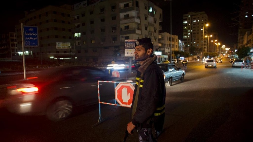 In this Tuesday, May 5, 2015 photo, a Palestinian Hamas police officer monitors the road as they set up a checkpoint at night in Gaza City. Still recovering from a devastating war with Israel last year, Gaza's Hamas rulers now find themselves confronting a new internal threat: jihadi militants who support the Islamic State group and appear intent on provoking Israel in order to pressure and embarrass Hamas. (AP Photo/Khalil Hamra)