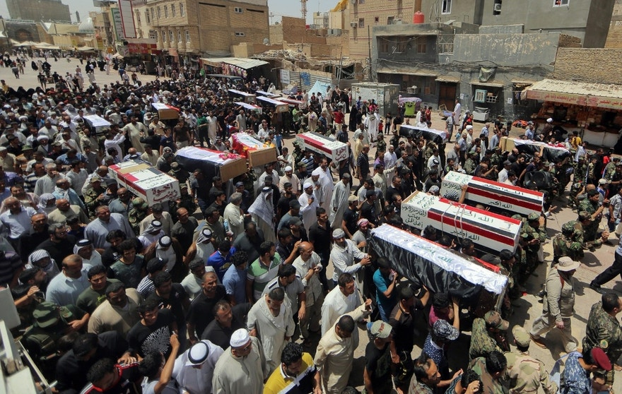 Mourners carry the flag-draped coffins of 15 militia members of a Shiite group, Asaib Ahl al-Haq, or League of the Righteous, who were killed in Beiji, Iraq, from fighting with Islamic State militants, according to their families, during the funeral procession in Najaf, 100 miles (160 kilometers) south of Baghdad, Monday, June 8, 2015. (AP Photo/Jaber al-Helo)