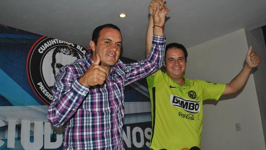 "Mexican soccer star Cuauhtemoc Blanco, left, gives the thumbs up sign during a news conference with Eduardo Bordonave, Morelos state president of the Social Democratic Party (PSD), in Cuernavaca, Mexico during election day Sunday, June 7, 2015.  Blanco has apparently been elected mayor of Cuernavaca, just south of Mexico City. Known for his pugilistic playing style, Blanco was equally combative at a victory news conference. ""Now I've screwed them,"" he said of his rivals. (AP Photo/Tony Rivera)"