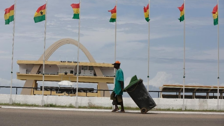 A man walk past Ghanaian flags flying at half mast  at the independence square in Accra, Ghana, Monday, June 8, 2015.  Ghana's president, John Dramani Mahama, has declared three days of mourning to begin Monday after a  gas station explosion and flooding in Ghana's capital that killed more than 150 people.  (AP Photo/Sunday Alamba)