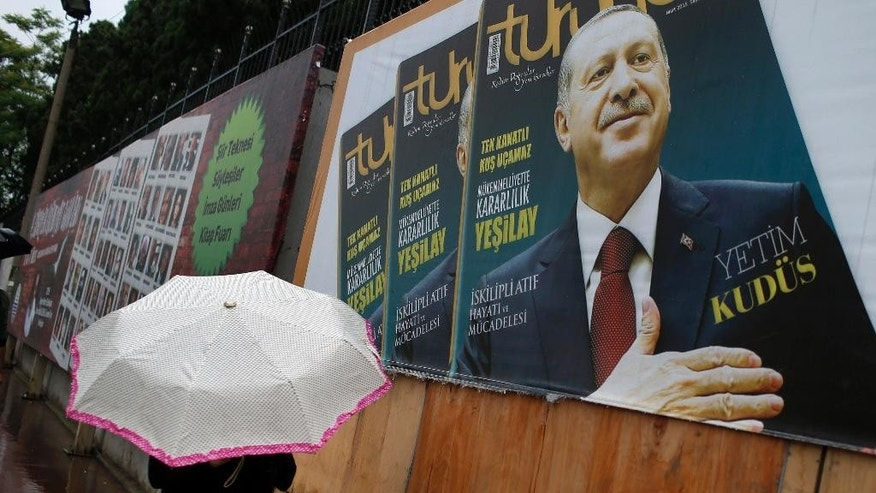 A man walks past a billboard with a picture of Turkey's President Recep Tayyip Erdogan, in Istanbul, Turkey, Monday, June 8, 2015. On elections held Sunday, June 7, 2015, Turkey's long-ruling party has suffered surprisingly strong losses in parliament that will force it to seek a coalition partner for the next government, but other parties vowed to resist any pact as election results flowed in Monday. Erdogan's Justice and Development Party, known as the AKP, won less than 41 percent of votes in Sunday's election for Turkey's 550-seat parliament. It was projected to take 258 seats, still top of the political heap but 18 below the minimum required to rule alone.(AP Photo/Emrah Gurel)