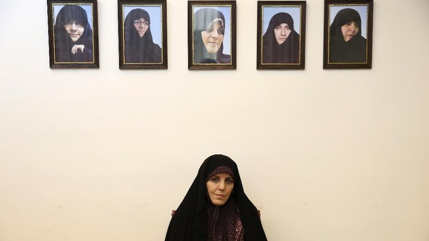 Vice President for Women and Family Affairs Shahindokht Molaverdi sits under portraits of her predecessors in an interview with The Associated Press at her office in Tehran, Iran, Monday, June 8, 2015. Molaverdi said a limited number of women will be allowed to watch Volleyball World League games in Tehran later this month as it lifts a ban on Iranian women attending male sporting events. (AP Photo/Ebrahim Noroozi)