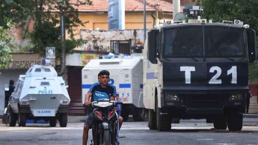 Youths ride a motorcycle past Turkish police vehicles blocking an area, in Diyarbakir, southeastern Turkey, Tuesday, June 9, 2015. Armed attackers in southeast Turkey killed the head of an aid organization linked to a Kurdish Islamist party on Tuesday, triggering rioting that led to the death of two other people, officials said.  A policeman and two journalists covering the incident in city of Diyarbakir were injured, according to the regional governor's office. There was no information on the two other victims. (AP Photo/Emre Tazegul)