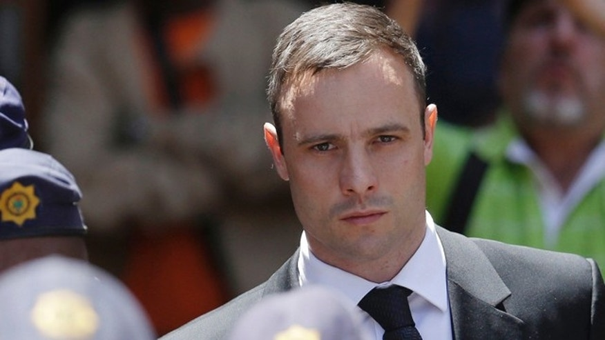 FILE - In this Friday, Oct. 17, 2014 file photo, Oscar Pistorius is escorted by police officers as he leaves the high court in Pretoria, South Africa. (AP Photo/Themba Hadebe, File)
