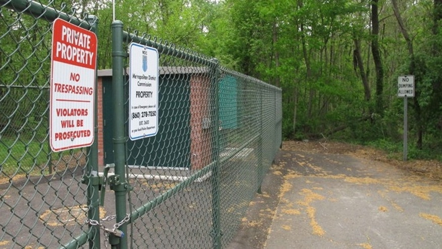 No trespassing and no dumping signs are posted in a neighborhood at the edge of a wooded area where the remains of seven people have been found since 2007 in Newington, Conn., Tuesday, May 12, 2015, Police believe a man serving prison time in Connecticut for manslaughter murdered all the victims, whose bodies were found in the woods just over the town line in New Britain, Conn. (AP Photo/Dave Collins)