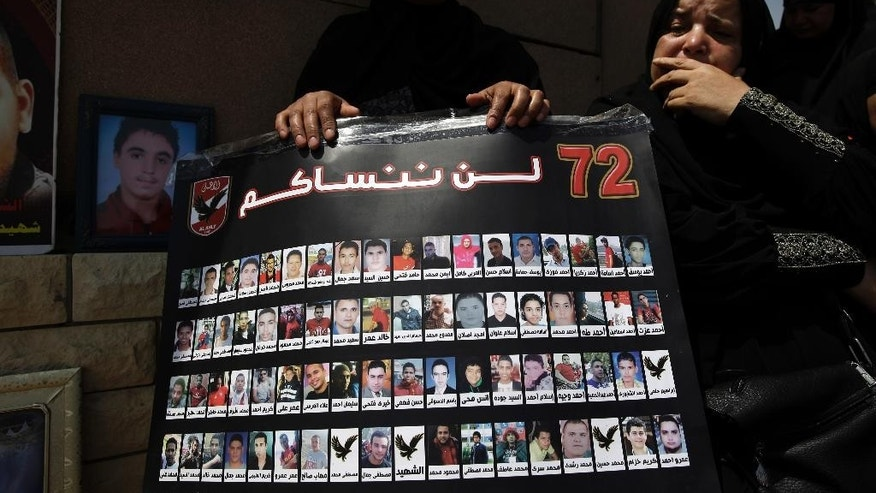 Families and supporters of the Al-Ahly club hold up a poster with the photos of victims as they await the verdict of the death sentences against 11 people for their role in a deadly 2012 soccer riot that killed more than 70 people in the city of Port Said, outside a police academy on the outskirts of Cairo, Egypt, Tuesday, June 9, 2015. A criminal court in Egypt's coastal city of Port Said on Tuesday sentenced 11 people to death over a 2012 soccer riot that left more than 70 dead and several hundreds injured. Arabic reads: 'We will not forget you'.  (AP Photo/Hassan Ammar)