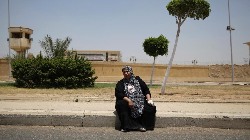 A mother of a supporter of the Al-Ahly club waits to hear the verdict against 11 people for their role in a deadly 2012 soccer riot that killed more than 70 people in the city of Port Said, outside a police academy on the outskirts of Cairo, Egypt, Tuesday, June 9, 2015. A criminal court in Egypt's coastal city of Port Said on Tuesday sentenced 11 people to death over a 2012 soccer riot that left more than 70 dead and several hundreds injured. (AP Photo/Hassan Ammar)
