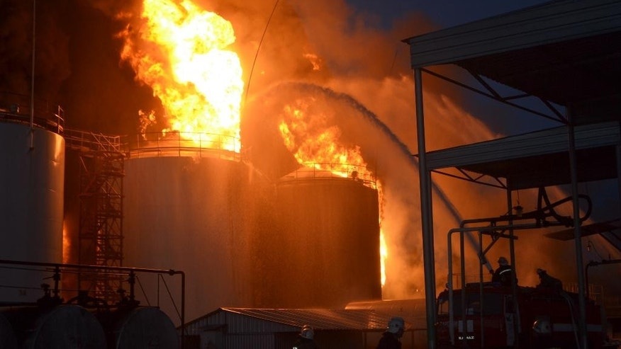 In this late Monday, June 8, 2015 handout photo made available by the Ukrainian Emergency Situations Ministry press service on Tuesday, June 9, 2015, Ukrainian firemen distinguish fire at a fuel depot near Hlevaha, Kiev region, Ukraine. At least one killed and a number of firemen were injured on Tuesday as they fought to control a blazing fuel depot outside Ukraine's capital Kiev. (AP Photo/Ukrainian Emergency Situations Ministry Press Service handout photo via AP)