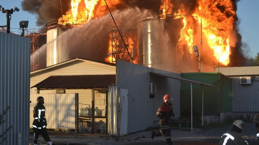 In this Tuesday, June 9, 2015, handout photo made available by the Ukrainian Emergency Situations Ministry press service Ukrainian firemen distinguish fire at a fuel depot near Hlevana, Kiev region, Ukraine. At least one killed and a number of firemen were injured on Tuesday as they fought to control a blazing fuel depot outside Ukraine's capital Kiev. (AP Photo/Ukrainian Emergency Situations Ministry Press Service handout photo via AP)
