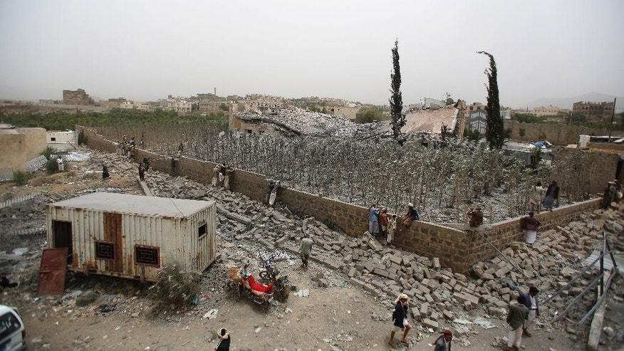 People watch the site of a house and its garden destroyed by a Saudi-led airstrike on the outskirts of Sanaa, Yemen, Tuesday, June 9, 2015. A series of airstrikes from the Saudi-led military coalition also targeted Yemen's Defense Ministry building, which is under control of Shiite rebels who control the capital, Sanaa, officials said. (AP Photo/Hani Mohammed)