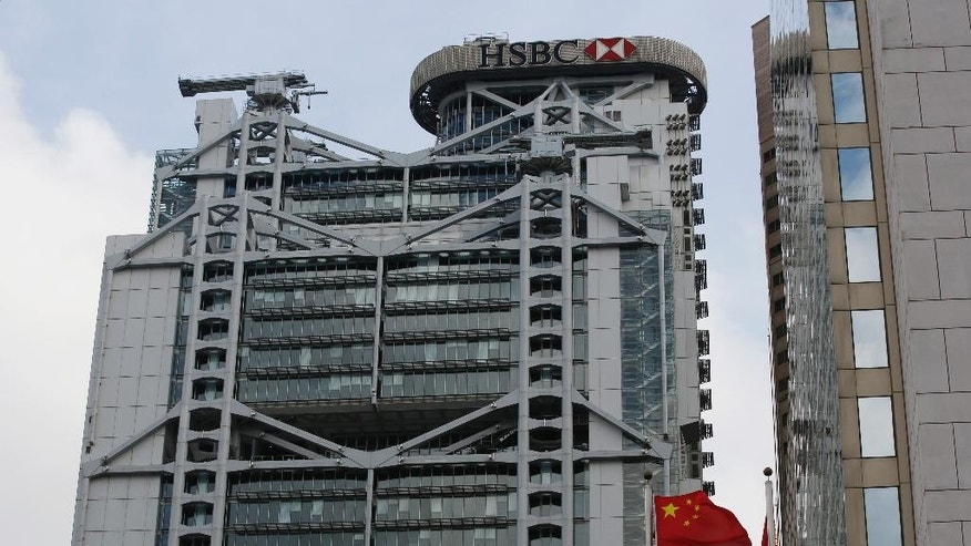 A Chinese flag and a Hong Kong flag blow in the wind  in front of the HSBC building in Hong Kong Tuesday, June 9, 2015. HSBC Holdings, Britain's largest bank by market value, will cut between 22,000 and 25,000 jobs around the world in an attempt to reduce costs and shift its center of gravity back toward fast-growing Asian economies. (AP Photo/Kin Cheung)