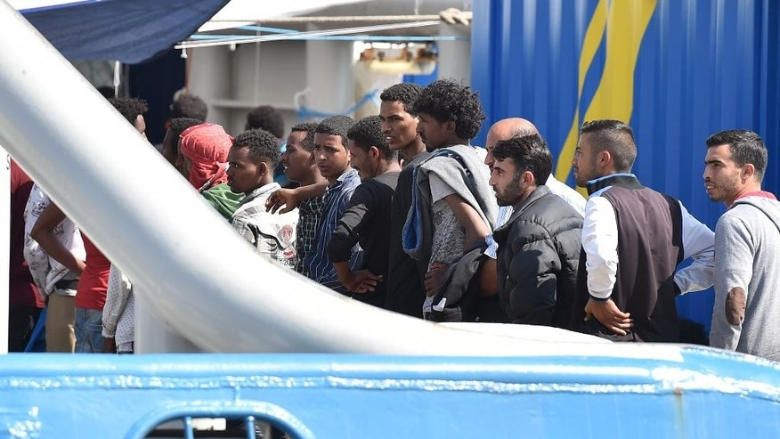 Rescued migrants stand on a deck of the Swedish Coast Guard ship KBV 001 Poseidon prior to being disembarked at the Messina harbor, Italy, Tuesday, June 9, 2015. Over the last weekend, nearly 6,000 migrants were rescued by an array of European military vessels, including 2,371 who were saved on Sunday from 15 boats that ran into difficulty shortly after smugglers set off with them from Libyan shores, the Italian coast guard said. (AP Photo/Carmelo Imbesi)