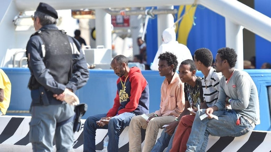 An Italian police officer stands next rescued migrants after they disembarked from the Swedish Coast Guard ship KBV 001 Poseidon at Messina harbor Italy, Tuesday, June 9, 2015. Over the last weekend, nearly 6,000 migrants were rescued by an array of European military vessels, including 2,371 who were saved on Sunday from 15 boats that ran into difficulty shortly after smugglers set off with them from Libyan shores, the Italian coast guard said. (AP Photo/Carmelo Imbesi)