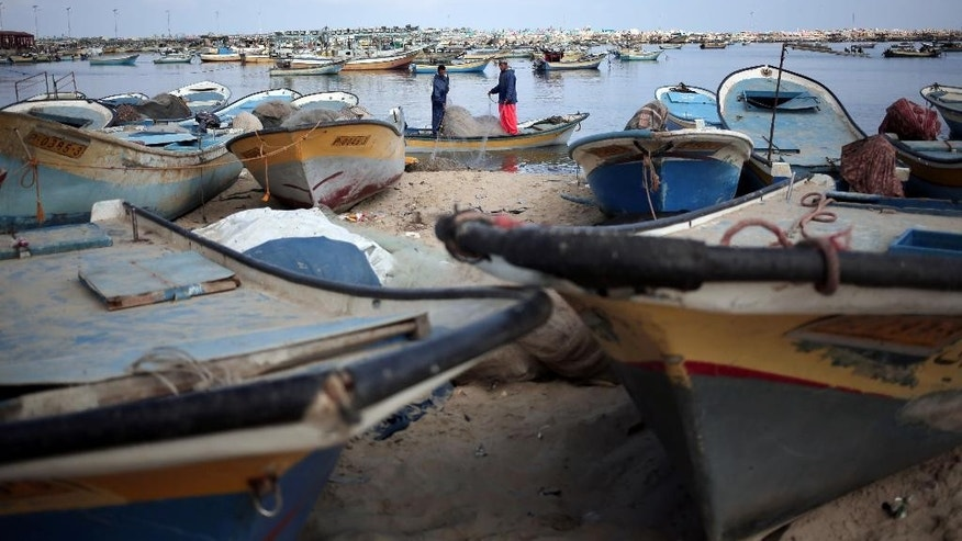 In this Friday, June 5, 2015 photo, two Palestinian fishermen clean up a fishing net while standing on a boat at the seaport of Gaza City. The Gaza Strip, with a 40-kilometer (25-mile) Mediterranean coastline, was always known for its seafood until Israel restricted the fishing area. As a result, Palestinians have begun importing fish and other seafood from Israel or Egypt and _ in recent years _ building fish farms. (AP Photo/Khalil Hamra)