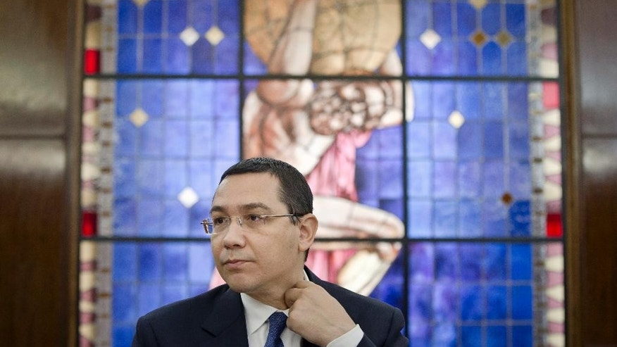 Romanian Prime Minister, Victor Ponta, adjusts his collar during a meeting with foreign media at the government headquarters in Bucharest, Romania, Tuesday, June 9, 2015. Parliament is to vote Tuesday on whether to lift Ponta's immunity protection for a corruption probe after anti-corruption prosecutors said he was suspected of corruption charges including being an accomplice to tax evasion from 2007 to 2008 while serving in Parliament, a conflict of interest and money laundering. (AP Photo/Vadim Ghirda)