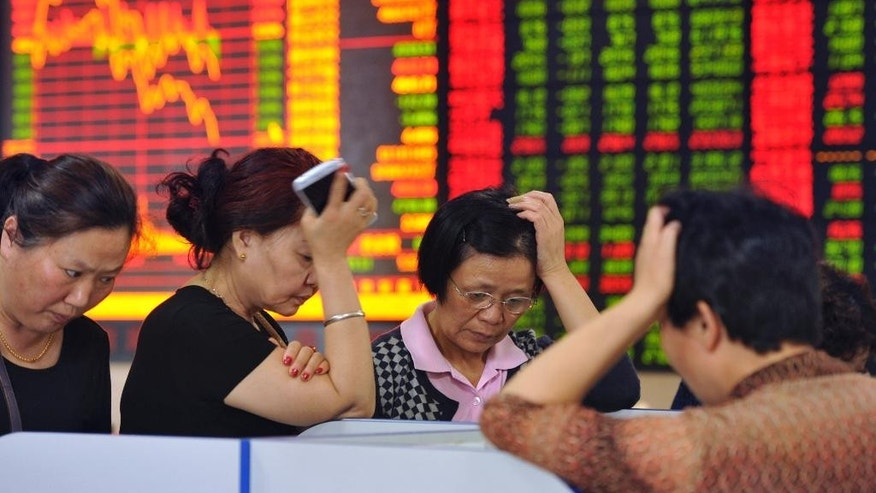In this photo taken May 28, 2015, Chinese stock investors react as prices fall at a brokerage house in Fuyang in central China's Anhui province. China's latest stock market boom began after the state press said last summer stocks were cheap. Investors took that to mean Beijing wanted prices to rise - and might prop up markets if needed. The benchmark Shanghai Composite Index has soared 140 percent over the past six months, though it has suffered stomach-churning drops along the way, most recently a 6.5 percent plunge May 28.(Chinatopix Via AP) CHINA OUT