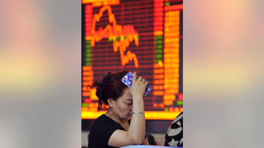 In this photo taken May 28, 2015, a Chinese stock investor reacts as prices fall at a brokerage house in Fuyang in central China's Anhui province. China's latest stock market boom began after the state press said last summer stocks were cheap. Investors took that to mean Beijing wanted prices to rise - and might prop up markets if needed. The benchmark Shanghai Composite Index has soared 140 percent over the past six months, though it has suffered stomach-churning drops along the way, most recently a 6.5 percent plunge May 28.(Chinatopix Via AP) CHINA OUT