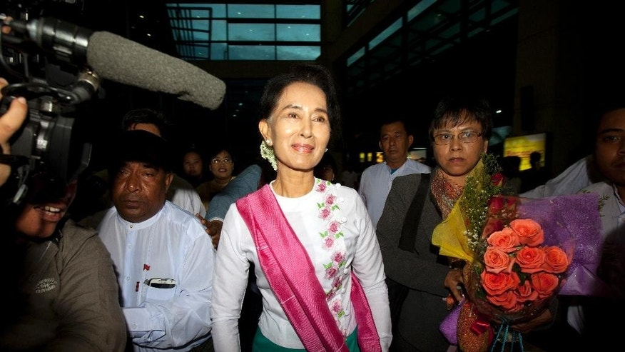 Myanmar's opposition leader Aung San Suu Kyi, center,  walks upon her arrival at Yangon International Airport to depart for China, Wednesday, June 10, 2015, in Yangon, Myanmar. Noble peace laureate Aung San Suu Kyi is making her first official visit to China from June 10 to 14 with the aim of promoting friendly relations and better understanding between the two neighboring countries, according to her party spokesman. (AP Photo/Khin Maung Win)