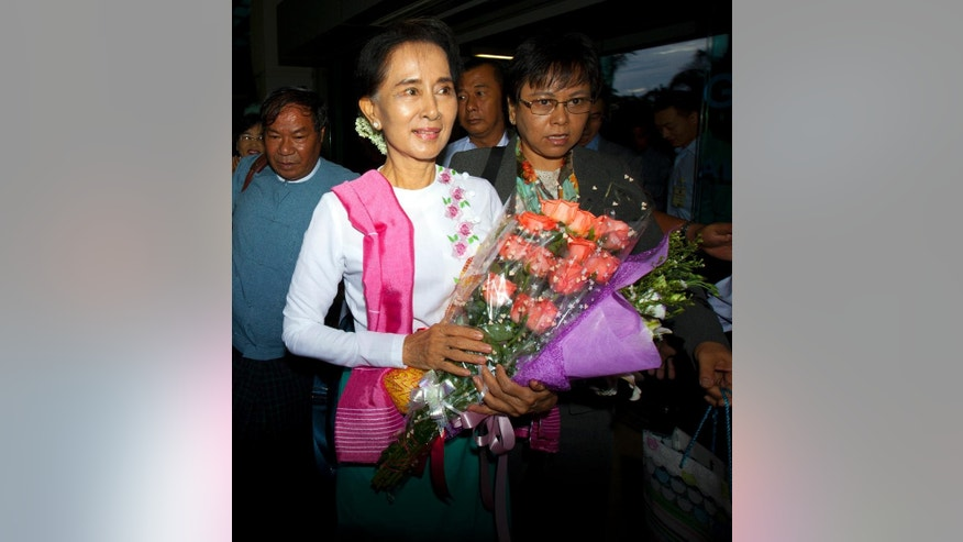 Myanmar's opposition leader Aung San Suu Kyi, center, arrives at Yangon International Airport to depart for China, Wednesday, June 10, 2015, in Yangon, Myanmar. Noble peace laureate Aung San Suu Kyi is making her first official visit to China from June 10 to 14 with the aim of promoting friendly relations and better understanding between the two neighboring countries, according to her party spokesman. (AP Photo/Khin Maung Win)