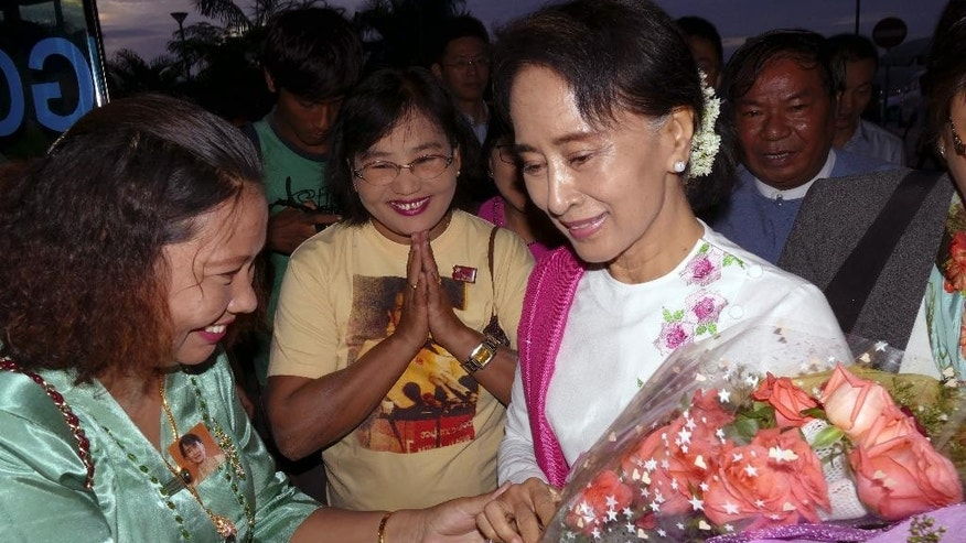 Myanmar's opposition leader Aung San Suu Kyi, right, receives flowers from a supporters of her National League for Democracy Party upon her arrival at Yangon International Airport to depart for China, Wednesday, June 10, 2015, in Yangon, Myanmar. Noble peace laureate Aung San Suu Kyi is making her first official visit to China from June 10 to 14 with the aim of promoting friendly relations and better understanding between the two neighboring countries, according to her party spokesman. (AP Photo/Khin Maung Win)