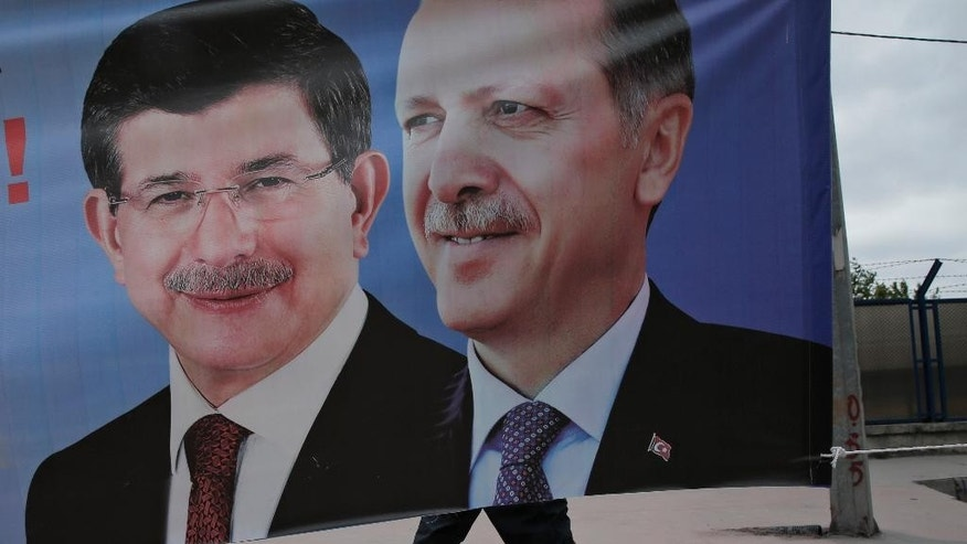 May 28, 2015: In this file photo, a man walks past a poster with pictures of Turkish Prime Minister and leader of the AKP party Ahmet Davutoglu, left, and Turkey's President Recep Tayyip Erdogan and party's former leader, right, in Istanbul, Turkey.