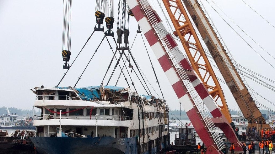 In this Sunday, June 7, 2015 photo, rescuers work on the raised capsized ship Eastern Star on the Yangtze River in Jianli county of southern China's Hubei province. China has assembled a 60-strong team to probe last week's river cruise ship sinking following orders from President Xi Jinping to find the cause of the country's worst maritime disaster in nearly seven decades. (AP Photo/Andy Wong)