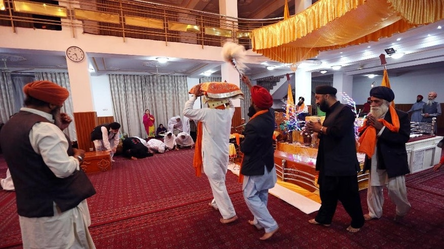 In this Sunday, May 31, 2015, photo, an Afghan Sikh, center, carries on his head a copy of the Guru Granth Sahib, the central religious text of Sikhism, during a service at a Gurdwara, the place of worship for Sikhs, in Kabul, Afghanistan. The once-thriving Sikh community is dwindling fast as many choose to leave the country of their birth to escape what they say is growing intolerance and discrimination. (AP Photo/Rahmat Gul)