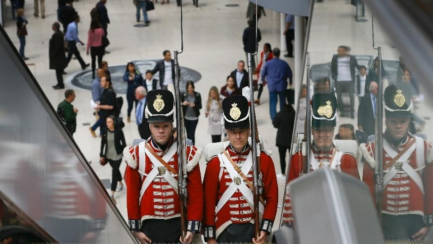 Re-enactors dressed as soldiers from the era of the Battle of Waterloo travel on an escalator after attending a memorial unveiling at Waterloo Station in London, Wednesday, June 10, 2015. The new war memorial honours all of the allied forces who fought at the Battle of Waterloo in 1815. The centrepiece is a giant replica of the reverse of the Waterloo Campaign medal. (AP Photo/Kirsty Wigglesworth)