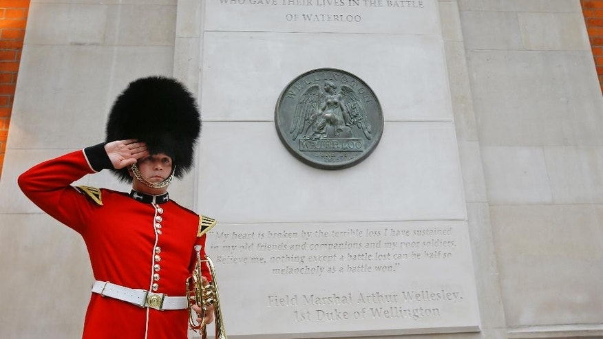 Bugler Lance Corporal Nick Walkley of the Band of the Welsh Guards salutes after playing the last post alongside the new memorial after it was unveiled at Waterloo Station in London, Wednesday, June 10, 2015. The new war memorial honours all of the allied forces who fought at the Battle of Waterloo in 1815. The centrepiece is a giant replica of the reverse of the Waterloo Campaign medal. (AP Photo/Kirsty Wigglesworth)