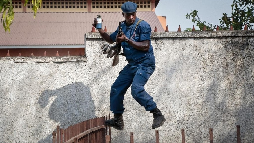 A policeman jumps as he tries to disperse a crowd of angry residents, after a man was killed by police and relatives were initially prevented from burying him in a timely manner in accordance with his Muslim beliefs, causing anger in his neighborhood, although permission for the burial was later granted, in the Buyenzi area of the capital Bujumbura, in Burundi Wednesday, June 10, 2015. Burundi's controversial presidential elections are now set for July 15. (AP Photo/Gildas Ngingo)