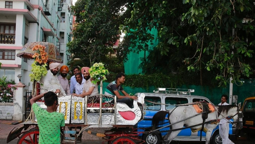 A man takes the picture of a group of Sikhs  taking a pleasure ride on a horse drawn carriage popularly known as 'victorias' in Mumbai, India, Tuesday, June 9, 2015. The horse drawn carriages are one of city's tourist attractions. (AP Photo/Rafiq Maqbool)