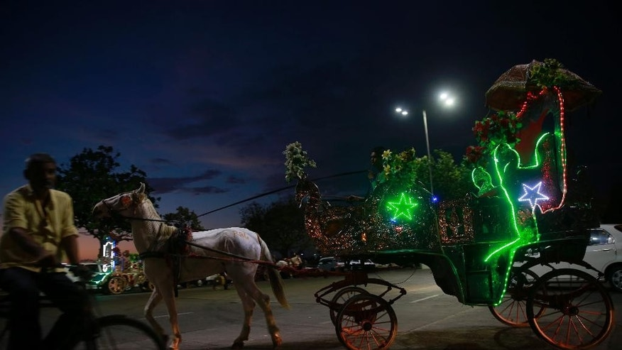 A family enjoys a ride on a horse drawn carriage popularly known as 'victorias' in Mumbai, India, Tuesday, June 9, 2015. The horse drawn carriages are one of city's tourist attractions. (AP Photo/Rafiq Maqbool)