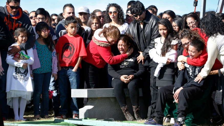 Laura Hernandez, center, is surrounded by family members at a gravesite service for her 17-year-old daughter, Jessica, in Westminster, Colo. on Saturday, Feb. 7, 2015. Police say Hernandez, 17, was shot Jan. 26 after she drove a stolen car toward an officer in a residential alley in Denver. A passenger in the car disputes the police account and says officers fired first. The shooting sparked protests and demands for an outside prosecutor to investigate what happened. (AP Photo/David Zalubowski)