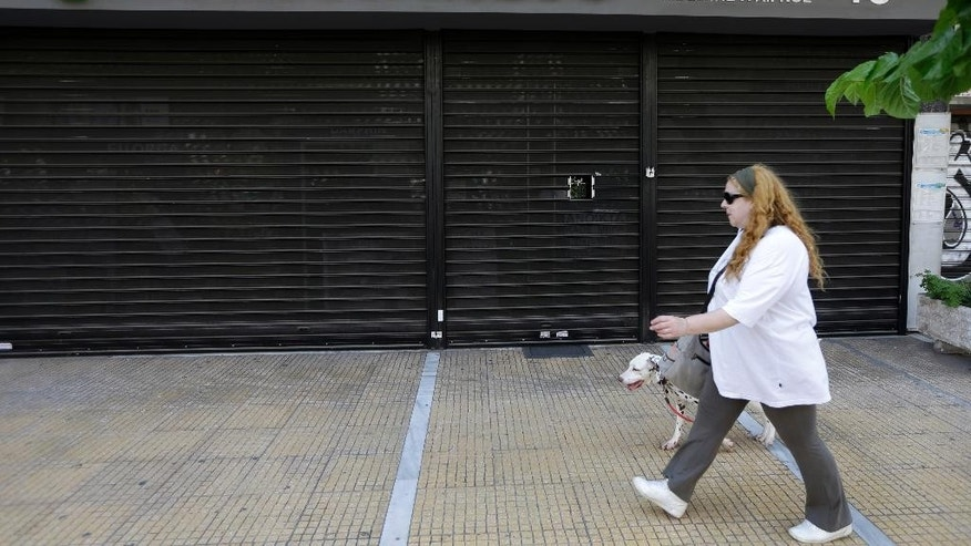 A woman with her dog passes a closed pharmacy during a 24-hour strike by pharmacists in Athens, Wednesday, June 10, 2015. Pharmacists oppose government proposals to allow supermarkets to sell medicines that don't require a medical prescription _ which currently can only be dispensed by pharmacies. Greece has three weeks left to conclude a deal with its creditors before its bailout program expires at the end of the month. (AP Photo/Thanassis Stavrakis)