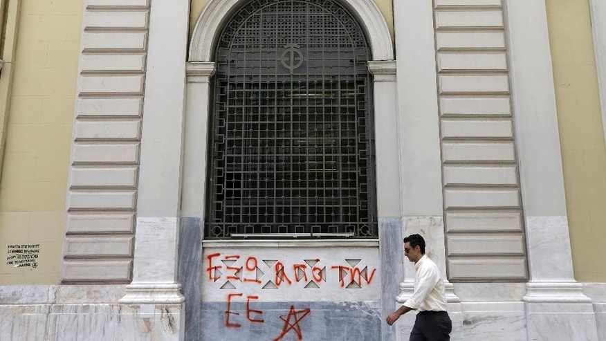 A pedestrian passes a sign reads ''Out of EU (European Union)'' at the headquarters of National Bank of Greece in Athens, Wednesday, June 10, 2015. Greece's prime minister was heading to Brussels on Wednesday hoping to meet with the leaders of Germany and France, in an effort to break a deadlock in bailout talks that have revived fears his country could default and drop out of the euro. (AP Photo/Thanassis Stavrakis)