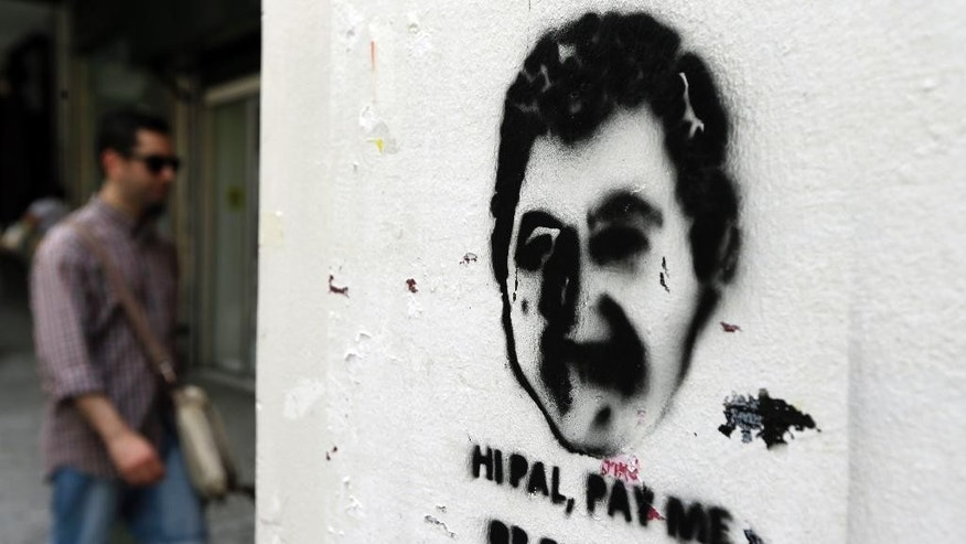 A pedestrian walks near stenciled graffiti in Athens, Wednesday, June 10, 2015. Greece's prime minister was heading to Brussels on Wednesday hoping to meet with the leaders of Germany and France, in an effort to break a deadlock in bailout talks that have revived fears his country could default and drop out of the euro. (AP Photo/Thanassis Stavrakis)
