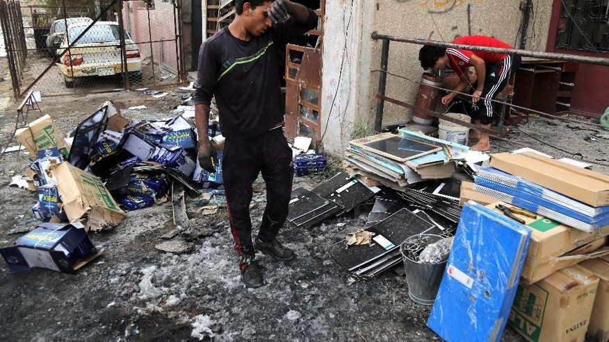 Iraqis clean up the site of a car bomb near restaurants and shop in Palestine Street in eastern Baghdad, Iraq, Wednesday, June 10, 2015. On Tuesday night, a series of bombings targeting public places and Iraqi security forces killing and wounding civilians. (AP Photo/Karim Kadim)