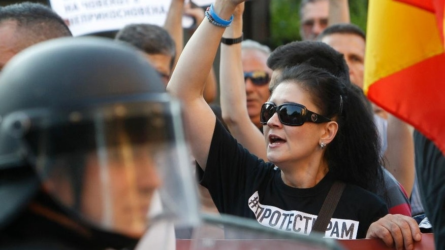 People protest in front of a police cordon set at the approach of the Interior Ministry in Skopje, Macedonia, on Saturday, June 6, 2015. Hundreds of people protested peacefully in Skopje on the fourth anniversary of the death of a 22-year-old Martin Neskovski, who was beaten by police during post-election celebrations, demanding resignation of the Prime Minister Nikola Gruevski and his cabinet. (AP Photo/Boris Grdanoski)
