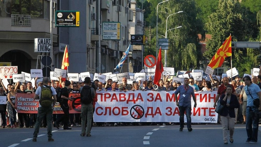 "People carry banners reading ""Justice For Martin, Freedom For Everyone"" and ""Resignation"" as they protest through a street in Skopje, Macedonia, on Saturday, June 6, 2015. Hundreds of people protested peacefully in Skopje on the fourth anniversary of the death of a 22-year-old Martin Neskovski, who was beaten by police during post-election celebrations, demanding resignation of the Prime Minister Nikola Gruevski and his cabinet. (AP Photo/Boris Grdanoski)"