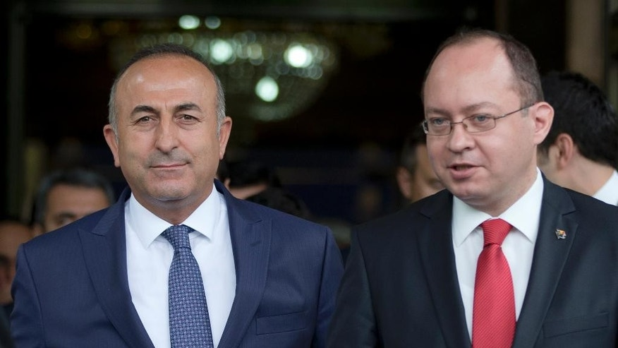 Turkish Foreign minister Mevlut Cavusoglu, left, walks next to Romanian counterpart Bogdan Aurescu, right, after a joint statement in Bucharest, Romania, Wednesday, June 10, 2015. Cavusoglu is on a two day visit to Romania.(AP Photo/Vadim Ghirda)
