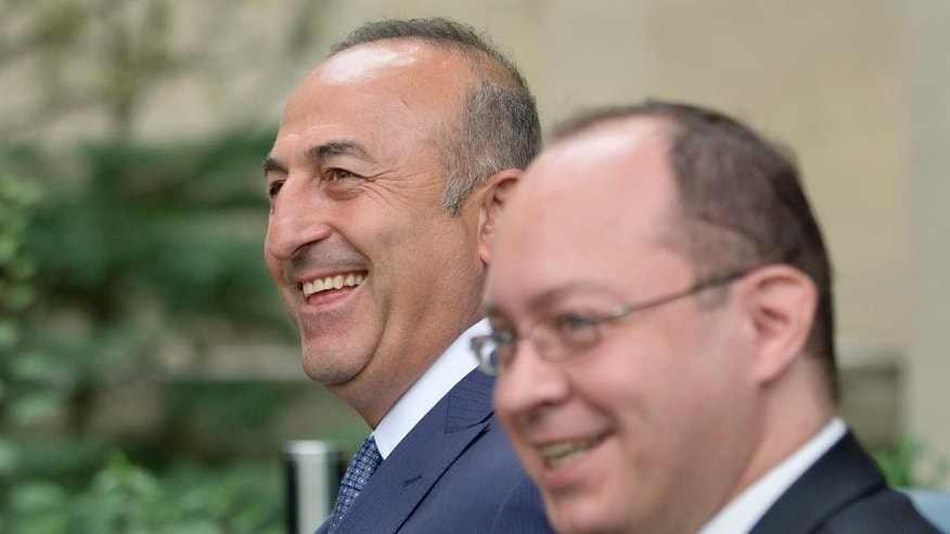 Turkish Foreign minister Mevlut Cavusoglu, left, smiles while walking next to Romanian counterpart Bogdan Aurescu, right, after a joint statement in Bucharest, Romania, Wednesday, June 10, 2015. Cavusoglu is on a two day visit to Romania.(AP Photo/Vadim Ghirda)