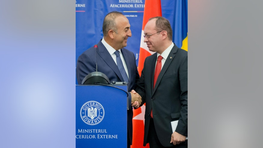 Turkish Foreign minister Mevlut Cavusoglu, left, shakes hands with Romanian counterpart Bogdan Aurescu, right, after a joint statement in Bucharest, Romania, Wednesday, June 10, 2015. Cavusoglu is on a two day visit to Romania. (AP Photo/Vadim Ghirda)