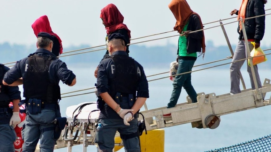 FILE - In this Monday June 8, 2015 file photo, rescued migrants disembark from the Irish Navy ship Le Eithne at the Taranto harbor, Italy. Heartened by recent election successes by an anti-immigrant party, Italian politicians based in the north vowed Sunday not to shelter any more migrants saved at sea, even as thousands more were being rescued in the Mediterranean from smugglers' boats in distress. (AP Photo/Gaetano Lo Porto, File)