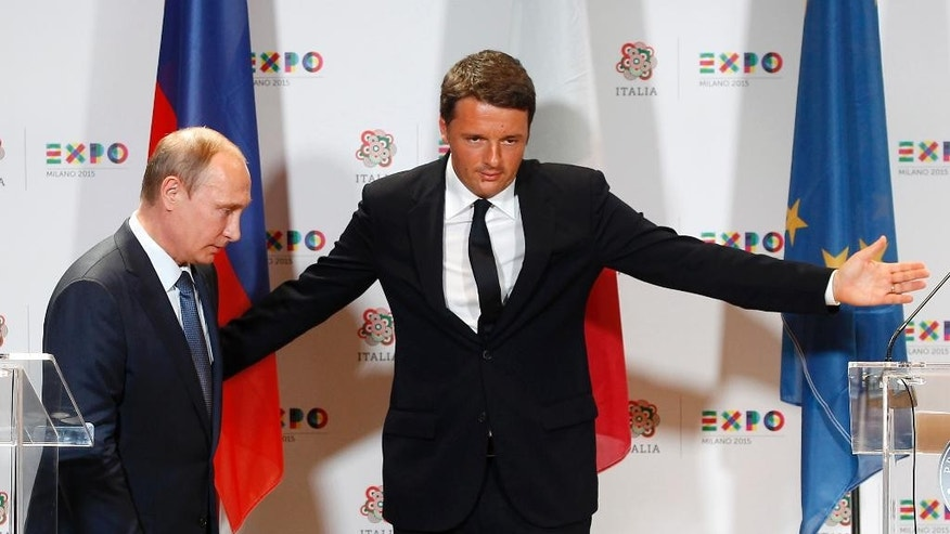 Italian Premier Matteo Renzi, right, greets Russian President Vladimir Putin at the end of a press conference, in Rho, near Milan, Italy, Wednesday, June 10, 2015.  Russian President Vladimir Putin was meeting Wednesday with Italian officials and Pope Francis as the U.S. sought to encourage the Vatican to join the West in condemning Moscow's actions in Ukraine. (AP Photo/Antonio Calanni)