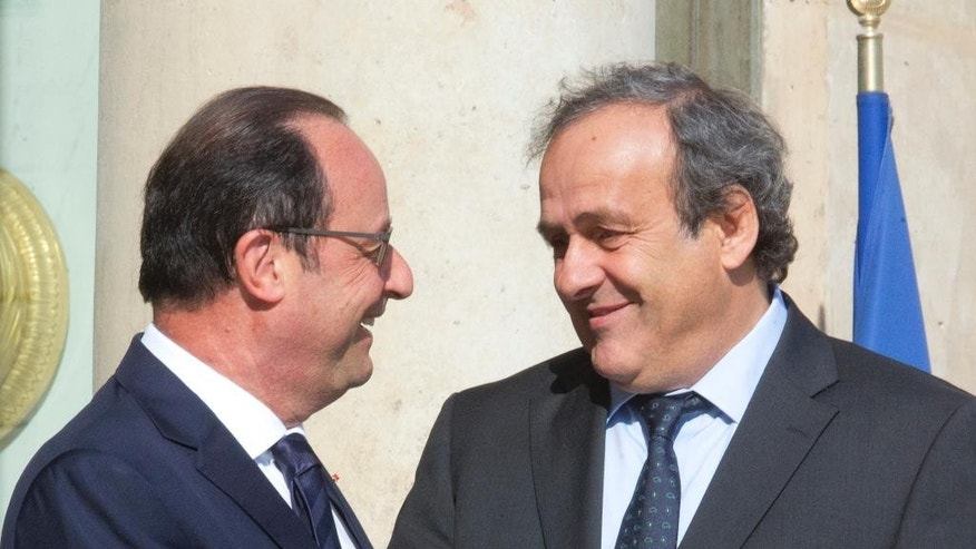 French President Francois Hollande, left, chats with European Soccer Federation UEFA President Michel Platini following their meeting at the Elysee Palace in Paris, France Wednesday, June 10, 2015. (AP Photo/Jacques Brinon)