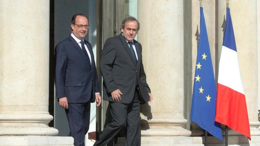 French President Francois Hollande, left, escorts European Soccer Federation UEFA President Michel Platini following their meeting at the Elysee Palace in Paris, France Wednesday, June 10, 2015. (AP Photo/Jacques Brinon)