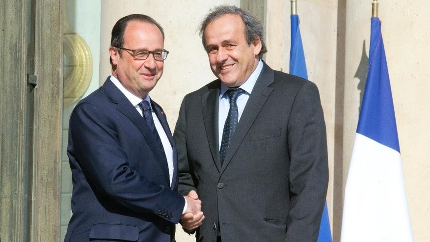 French President Francois Hollande, left, shakes hands with European Soccer Federation UEFA  President Michel Platini following their meeting at the Elysee Palace in Paris. France Wednesday, June 10, 2015. (AP Photo/Jacques Brinon)